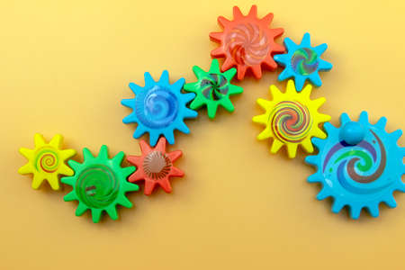 Colored plastic gears on an orange background, top view. Communication and teamwork concept.