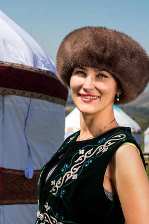 independent mongolia: Kazakh girl in national clothes standing near the yurt