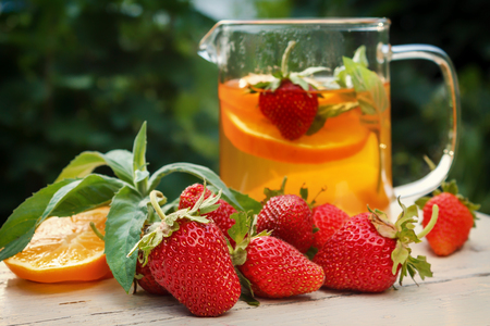 Tea with lemon and strawberries in the garden on a wooden table. Rustic