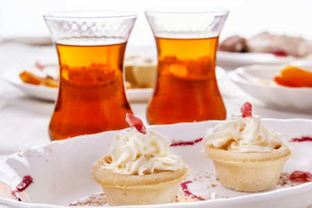 Cake with whipped cream and tea in glass glasses. A high key. Soft light