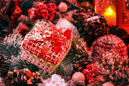 Christmas gift covered with snow in the light of a red lantern on the background of New Years scenery Stock Photo
