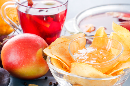 Winter alcoholic drinks - mulled wine, punch, grog with cornflakes Glass glasses with mulled wine. Hot fruit tea. Spices, fruit. Stock Photo