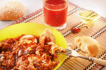 Ragout of eggplant and stewed vegetables with boiled eggs. A fork with a piece of egg. Fresh juice and bread. Dietary food