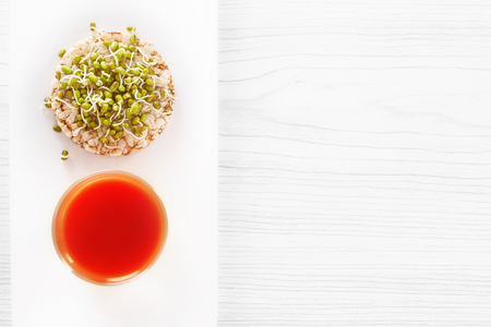 Healing food - sprouted grains, puffed wheat cake and fresh tomato juice. View from above Stock Photo