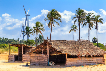 huts of palm leaves in the jungle against the background of a modern wind generator. blue sky, tropics