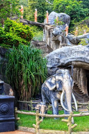 Symbols of Buddhism - sculptures of elephants, statues of monks on the territory of the temple in the rainforest