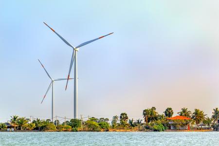 Wind generators in a jungle on a lake near a blue sky Stock Photo