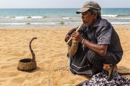 Colombo, Sri Lanka - January 11, 2018. Snake charmer plays on the beach on a sunny day