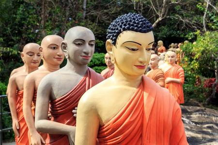 Estatuas de monjes budistas en fila para adorar al Buda