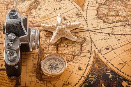 Starfish, a compass and an old camera lie on vintage map. Copy space. Stock Photo