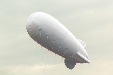 White inflatable dirigible with a place for a logo on a background of a gray sky with clouds Stock Photo