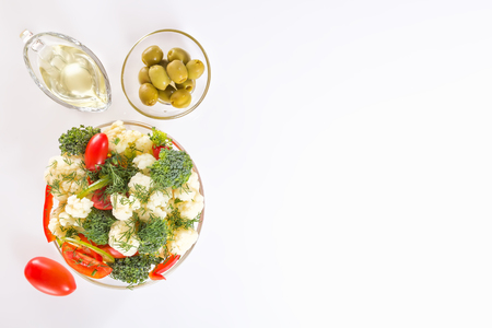 Fresh salad of cauliflower with tomato, vegetables, broccoli, greens and olives in a glass bowl with a glass nipple on a white background. Top view. Copy space