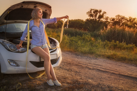 beautiful blonde girl sits with a towline on a hood of a broken car on a rural road in the rays of the sunset. Toned. Copy space