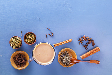 Traditional Indian tea masala with milk and spices on a blue background. Top view. Copy space