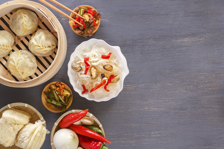 Chinese food on a gray wooden table. Traditional steam dumplings, noodles, vegetables, seafood. Top view. Copy space Stock Photo