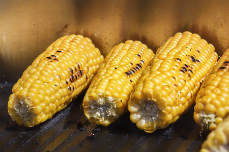 Grilled corn on the grill. Cooking food on the street