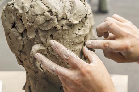 beeldhouwer maakt een buste en legt zijn handen met klei op het skelet van de sculptuur. Detailopname