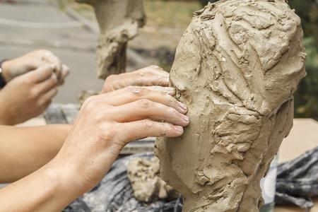 le sculpteur crée un buste et pose ses mains d'argile sur le squelette de la sculpture. Fermer Banque d'images