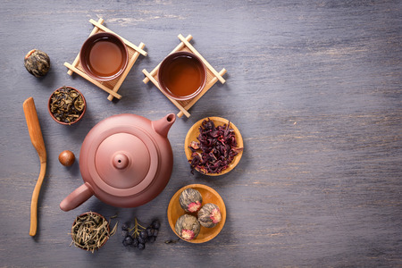Several types of green tea, black tea, hibiscus tea and tea ceremony attributes - a ceramic teapot, cups, a strainer, chopsticks and tweezers are placed on an old wooden table. Top view Copy space