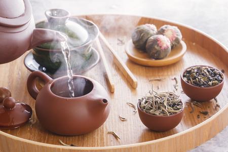 Bei einer traditionellen Teezeremonie wird kochendes Wasser in eine Keramik-Teekanne gegossen. Nahansicht Standard-Bild