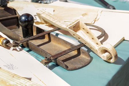 Plane, wooden blanks and tools lie on the table of the carpentry workshop on a sunny day. Close-up