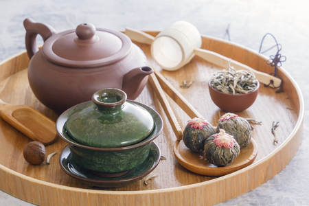 Green tea and tea ceremony attributes - ceramic teapot, cups, strainer, chopsticks and tweezers placed on a wooden tray