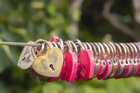 Locks of love in the shape of a heart hang on a steel cable of a pedestrian bridge Reklamní fotografie