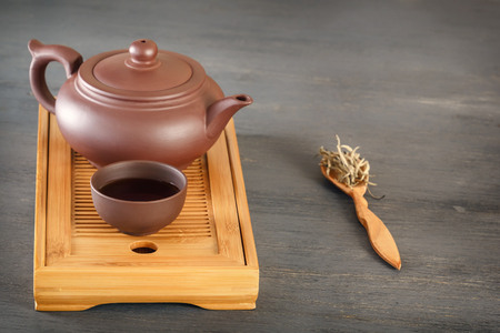 Traditional asian ceramic teapot with a cup stand on a special wooden tea tray on a gray table