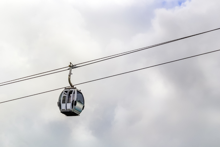 Cable car for the transportation of tourists moves against the backdrop of clouds. Copy space