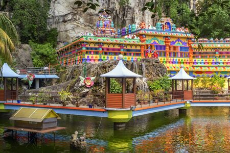 Kuala Lumpur, Malaysia - December 30, 2018. Pond with artificial waterfalls, bridges and gazebos for relaxing on the background of a Hindu temple in the Batu caves complex Redakční