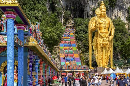 Kuala Lumpur, Malaysia - December 30, 2018. Giant sculpture of the Golden Buddha at the main entrance to the complex of Batu caves on a sunny day
