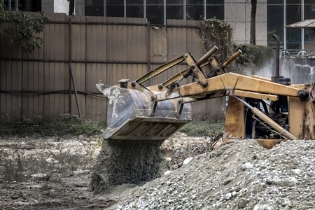 bulldozer at the construction site pours rubble. Toned.
