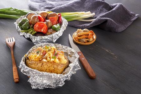 Patatas al horno con tocino, cebollas y verduras al horno en papel de aluminio: tomates, berenjenas, pimientos en una mesa de madera gris. Foto de archivo