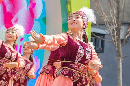 Almaty, Kazakhstan - March 23, 2019.Beautiful girls in national Kazakh costumes dance on the street celebrating Nauryz holiday