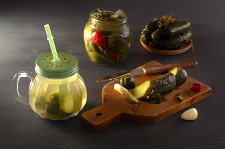 Cucumber pickle in a jar with a lid and tube and pickled cucumbers in a plate on a wooden table. Close-up Stock Photo