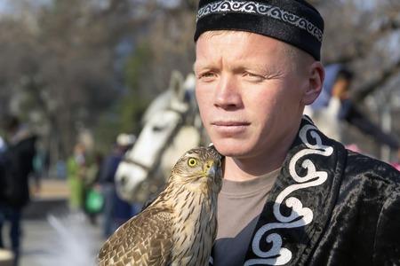 Almaty, Kasachstan - 21. März 2019. Falcon sitzt auf der Hand eines Jägers, der in der nationalen kasachischen Kleidung gekleidet ist - Berkutchi. Porträt. Nahaufnahme