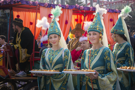 Almaty, Kazakhstan - March 21, 2019. Beautiful girls in national Kazakh clothes are holding trays with a traditional dish - baursaks during a costume festive procession