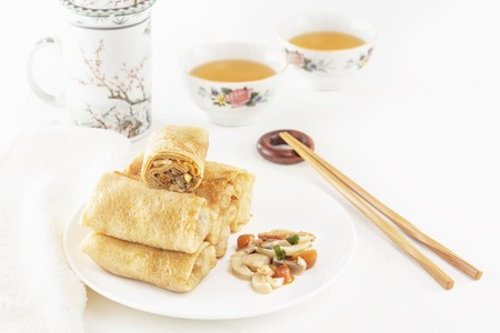 Traditional Chinese tortillas filled - bings in a plate with mushrooms on a white background, cups of tea. Copy space