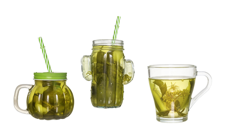 Two glass jars with a straw and a glass of cucumber pickle isolated on white background 免版税图像
