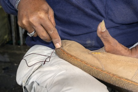 Shoemaker mends shoes in a street shop. Close-up