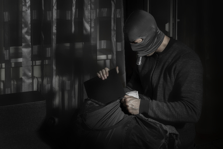 Thief in a mask and with a flashlight in the room puts the loot in a big bag