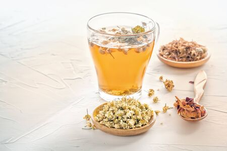 Herbal tea with pharmaceutical chamomile, dry chrysanthemum and hunters on a white table. Copy space
