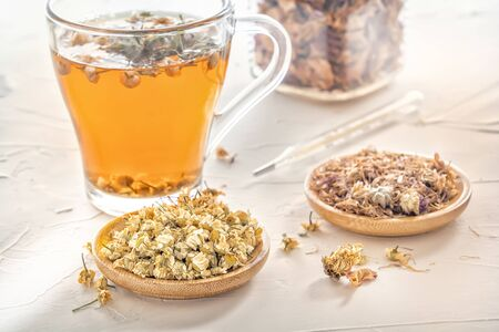 Herbal tea with pharmaceutical chamomile, dry chrysanthemum and hunters on a white table