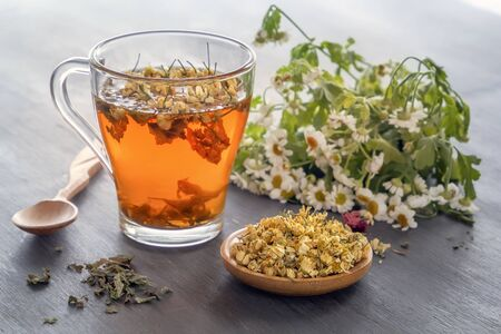 Herbal tea with pharmaceutical chamomile on a gray wooden table. Close-up