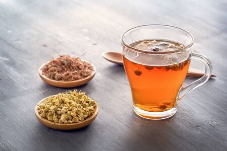 Herbal tea with pharmaceutical chamomile and dry chrysanthemum on a gray wooden table
