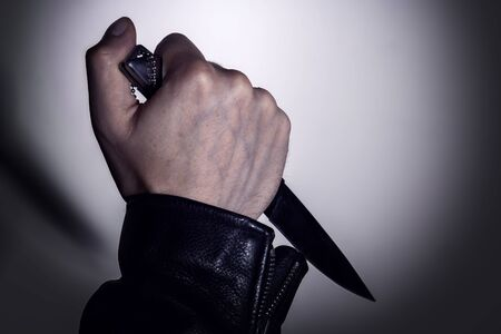 Hand with a knife on the background of the wall with the shadow of a knife. Copy space