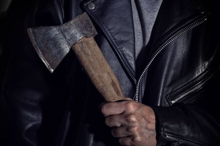 Male hand holds an ax on the background of a leather jacket. Close-up