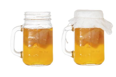 Homemade fermented drink Kombucha in a glass jug and jar. Isolated on white background
