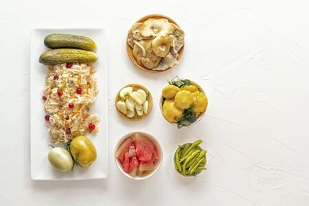 Fermented products cabbage, peppers, pickles, tomatoes, mushrooms, squash, garlic on a white table. Top view. Copy space