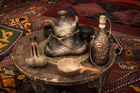 Traditional Kazakh dishes for drinks made of wood and leather are on an old wooden table in a yurt - the home of nomads. Close-up